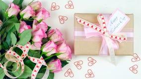 Generi le spese generali del giorno del ` s con il regalo e le rose rosa sul fondo di legno bianco della tavola immagine stock