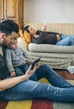 Generi lo sguardo della compressa con il piccolo figlio mentre la madre incinta guarda il cellulare fotografia stock