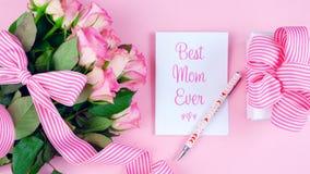 Generi mai le spese generali del giorno del ` s con le rose, la migliore carta della mamma ed il regalo sulla tavola rosa fotografie stock