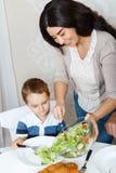Generi mettere l'insalata sul piatto di suo figlio Fotografia Stock Libera da Diritti