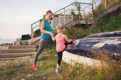 Generi mostrando alla figlia come allungare facendo uso di una barca sulla spiaggia Fotografia Stock