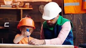 Generi, parent con la barba che insegna al piccolo figlio ad utilizzare il cacciavite dello strumento Ragazzo, bambino occupato i video d archivio
