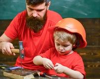 Generi, parent con la barba che insegna al piccolo figlio ad utilizzare le bullette per suole ed il martello Ragazzo, bambino occ Fotografia Stock