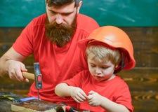 Generi, parent con la barba che insegna al piccolo figlio ad utilizzare le bullette per suole ed il martello Ragazzo, bambino occ Immagine Stock Libera da Diritti