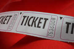 Generic Blue Tickets on a Red Background. Photograph of a generic blue ticket on a red fabric background royalty free stock photography