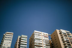 4 generic building facades with blue sky in the background. Stock Photos