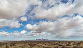 Generic Desert Scene. Generic arid desert scene together with cumulus clouds above royalty free stock photo