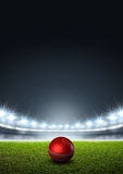Generic Floodlit Stadium With Cricket Ball. A generic stadium with an unmarked green grass pitch at night under illuminated floodlights and a red cricket ball royalty free illustration