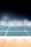 Generic Floodlit Stadium. A generic indoor stadium with an unmarked wooden court at night under illuminated floodlights royalty free stock images