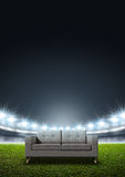 Generic Floodlit Stadium. A modern sofa in the middle of a generic stadium with an unmarked green grass pitch at night under illuminated floodlights stock images