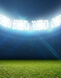 Generic Floodlit Stadium. A generic stadium with an unmarked green grass pitch at night under illuminated floodlights stock photography