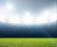 Generic Floodlit Stadium. A generic stadium with an unmarked green grass pitch at night under illuminated floodlights stock photo