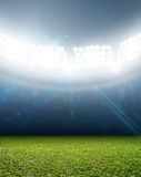 Generic Floodlit Stadium. A generic stadium with an unmarked green grass pitch at night under illuminated floodlights stock image