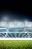 Generic Floodlit Stadium. A generic stadium with an unmarked green grass pitch at night under illuminated floodlights royalty free stock image