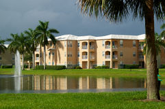 Generic Florida Apartment Complex. Looking across a pond towards a three story apartment complex in Naples, Florida, with a stormy sky and sunlight on buildings Stock Photos
