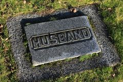 Generic Grave Marker Labeled Husband. A generic grave marker in a cemetery, labeled: husband Royalty Free Stock Photography