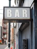 Generic inner city vibe BAR sign with tons of character. Bar sign with lots of inner city grunge vibe, white lettering, grey wall background and a little bit of Stock Images