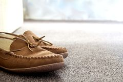 Generic mens suede moccasin slippers on carpet next to sofa in a Stock Photography