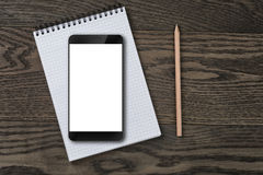 Generic modern smartphone on notepad with pencil Royalty Free Stock Image