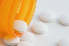 Generic Prescription Drugs. Prescription bottle with generic white pills spilling from it Royalty Free Stock Photo