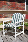 A generic PVC constructed lawn chair on a wood deck Royalty Free Stock Images
