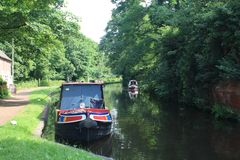 Life on the waterways. Generic shot of Trent & Mersey canal with narrowboats. A peaceful scene with towpath, reflections in the still water and green trees and royalty free stock images