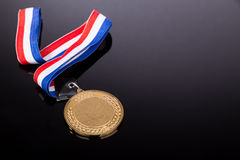 Generic sporting event gold medal with red and blue ribbon Royalty Free Stock Images