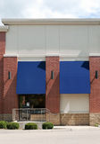 Generic Store Front. Facade of a generic store front entrance of red brick with blue awnings Royalty Free Stock Photos
