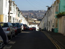Generic Street in Brighton, United Kingdom. Colourful image featuring a car coming up a road. The road has many painted houses in the foreground and there is an stock image