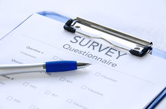 Generic survey questionnaire on clipboard with pen. Generic survey questionnaire clipped to a blue clipboard with a pen sitting on it Royalty Free Stock Photo