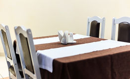 Generic view of restaurant table with table covered by tablecloth anf napkins on it Royalty Free Stock Photo