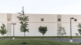 Generic Warehouse Office Complex Buildilng with Green Lawn and Streetlamps stock photos
