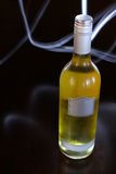 Generic White Wine Bottle. Generic wine bottle lit only by a torch. Light patterns in the background Royalty Free Stock Photo