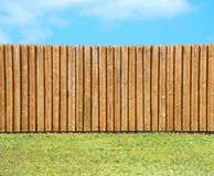 Generic wooden residential privacy fence with green grass yard Stock Photos