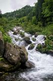 A generic woodland river scene with fast flowing river, rocks and green trees vegetation royalty free stock image