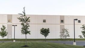 Generischer Lager-Bürokomplex Buildilng mit grünem Rasen und Straßenbeleuchtung stockfotos