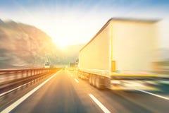 Generiska halva lastbilar som rusar på huvudvägen på solnedgången Arkivfoto