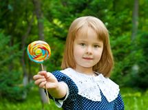 Generosity. Small cute girl stretches big sweet outdoors Royalty Free Stock Photo