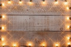 Generous copy space on old wooden planks with twinkling lights f. Generous copy space on old wooden planks with twinkling hazy lights frame - warm shades royalty free stock photography