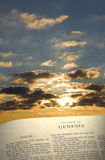 Genesis Book & Sky. Vertical image of  the Book of Genesis…in the beginning with morning sun and clouds in the background Stock Photo