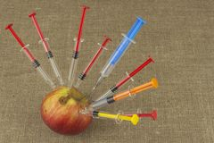 Genetic modification concept. Fruit and syginge. Apple receiving an injection of some substance for rapid ripening. Royalty Free Stock Image