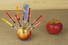 Genetic modification concept. Fruit and syginge. Apple receiving an injection of some substance for rapid ripening. Chemistry in the agricultural industry Stock Photos