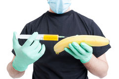 Genetically modified banana and syringe in male hands Stock Photos