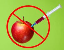 Genetically modified Red Apple. With syringes on green background.Stop injecting GMO in apple, fruit concept minimal royalty free stock images
