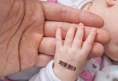 Genetisch kloonconcept De mens houdt hand van een baby met mede bar stock afbeelding