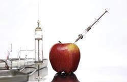 Genetycznie zmodyfikowani foods, jabłko pompujący z substancjami chemicznymi zdjęcie royalty free