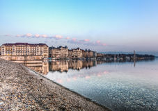 Geneva City. View of the buildings along Geneva lakefront from the beache of Bains des Paquis, on a calm morning Stock Image