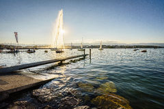 The Geneva city. The famous Water Fountain ( Jet dEau ) in Geneva with a beautiful sunset in the background. Photo taken on: Juillet 03rd, 2015 royalty free stock photo