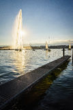 The Geneva city. The famous Water Fountain ( Jet dEau ) in Geneva with a beautiful sunset in the background. Photo taken on: Juillet 03rd, 2015 stock photo
