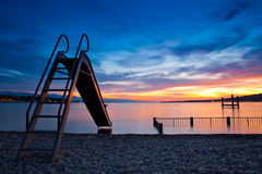 Geneva Cityscape. Playground slide into the Lake in the swimming area at Lake geneva, Switzerland Stock Photography